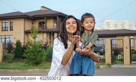 Smiling Brunette Young Woman And Little Asian Girl Boast Of Keys Of New Apartment Against Dwelling B