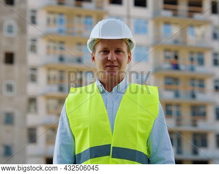 Contractor Portrait Looking At Camera Against Multistory Building