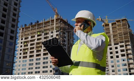 Foreman Checking Plans And Talking On Phone On Construction Site