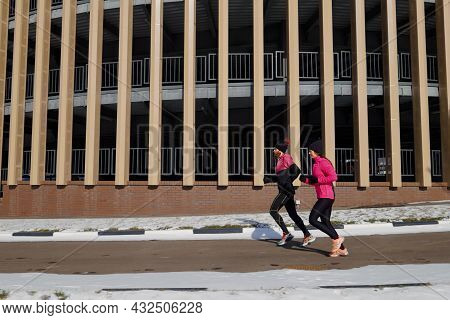 Fit Couple Jogging Around Building In City