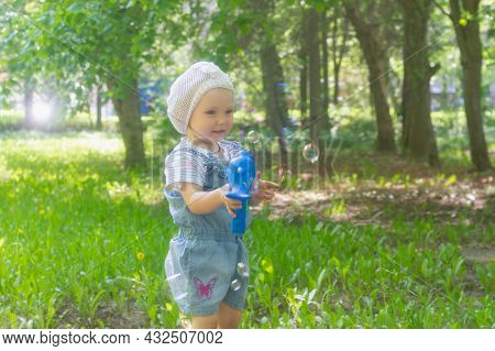 Cute Girl 2 Years Old In The Park In The Summer Blows Soap Bubbles From A Musical Gun.