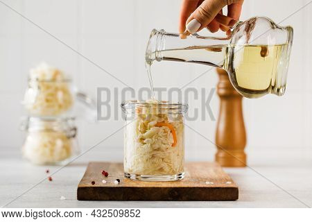 A Womans Hand Pours Vegetable Oil On Sauerkraut In A Glass Jar. Fermentation And Canning Of Vegetabl