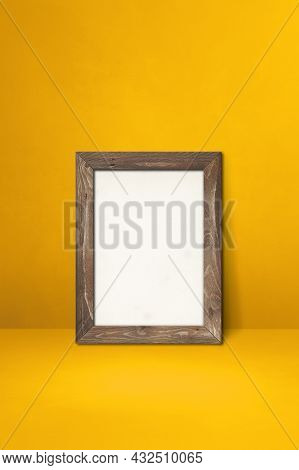 Wooden Picture Frame Leaning On A Yellow Wall. Blank Mockup Template
