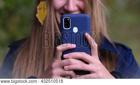 Young Girl Holds The Phone In Her Hand, Takes Pictures On The Phone. The Face Is Unrecognizable. Mob