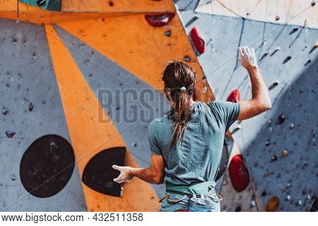 Young Man Professional Climber Assists Someone On Climbing Wall At Training Center In Sunny Day, Out