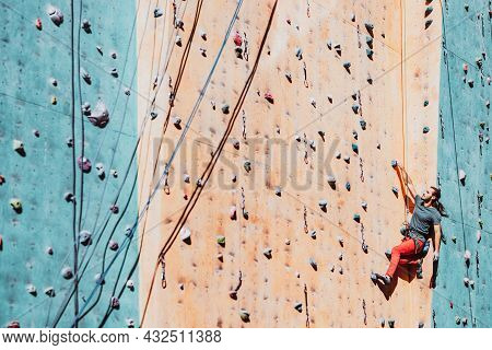 One Caucasian Man Professional Sportsman, Male Climber Workouts On Climbing Wall At Training Center