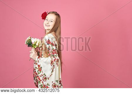 Fashion Portrait Of A Beautiful Elegant Girl In A Pretty Dress With Flowers On Pink Background. Youn