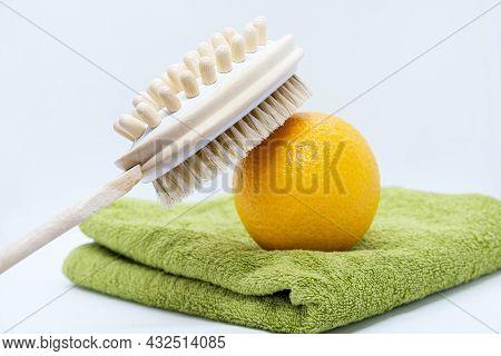 Orange And Double-sided Massage Brush For Body And Orange On Green Towel On White Background. Anti-c