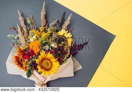 Fall Bouquet Of Yellow Red Orange Flowers Wrapped In Paper And Arranged On Grey And Yellow Backgroun