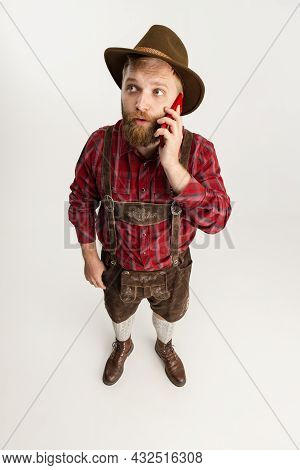 Young Bearded Man, Waiter In Traditional Bavarian Costume Using Phone Isolated Over White Studio Bac