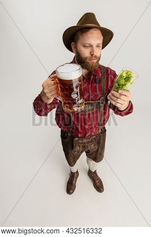 Young Bearded Man, Waiter In Traditional Bavarian Costume Holding Beer Glasses Filled With Wild Hot