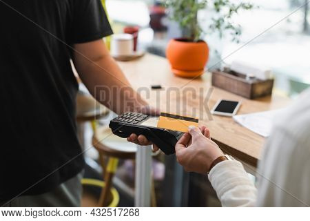 Partial View Of Waiter Holding Payment Terminal Near Client With Credit Card In Cafe