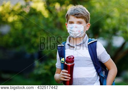 Happy Little Kid Boy, Medical Mask, Water Bottle And Backpack Or Satchel. Schoolkid On Way To School