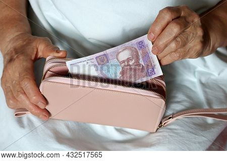 Elderly Woman Takes Out Ukrainian Hryvnia From Her Wallet Sitting In Bed, Wrinkled Female Hands Clos