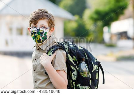 Happy Kid Boy With Glasses And Medical Mask Due To Corona Virus Covid Pandemic. Schoolkid With Satch