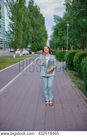 A Beautiful Girl Walking On The Sidewalk With A Laptop