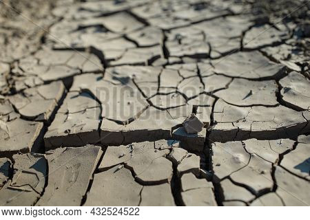 White Dried And Cracked Ground Earth Background. Closeup Of Dry Fissure Ground. Gray Crack On Earth