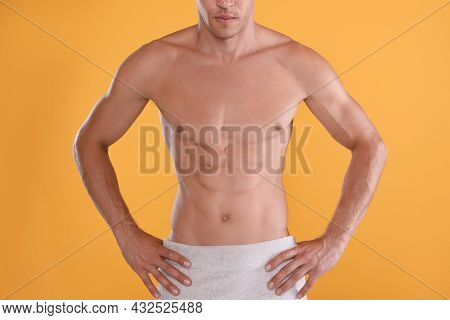 Shirtless Man With Slim Body And Towel Wrapped Around His Hips On Yellow Background, Closeup