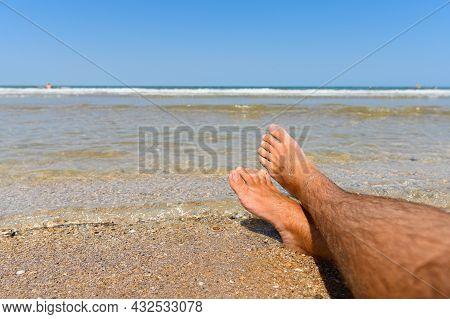 Male Legs On The Beach Next To The Sea. Ideal Seaside Resort Concept. Selective Focus On Legs.