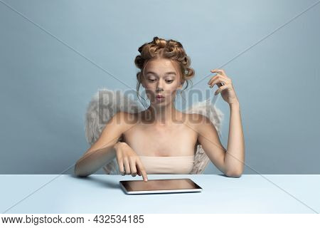 Portrait Of Young Beautiful Girl In Image Of Angel With Wings Using Gadget, Tablet Isolated On Blue