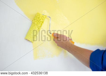 Millennial Man Painting Wall In Yellow Color With Roller. Renovation, Repair And Redecoration Concep