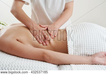 Back Massage. Masseur Massaging Young Woman On Massage Table In Spa Salon. Young Woman Relaxing Duri