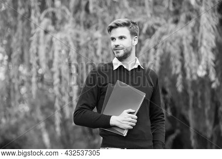 Handsome Unshaven Man With A Workbook In His Hands Staring Into The Distance Outdoor, Knowledge Day