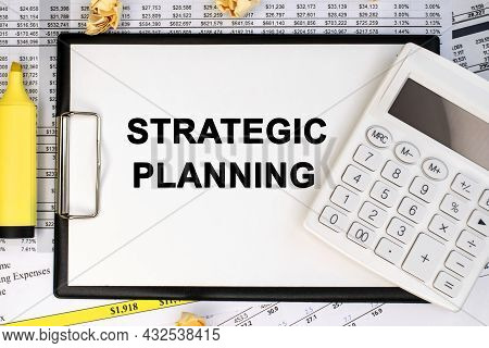 Strategic Planning Is Written On A Stationery Tablet That Lies On A Financial Document Near A White
