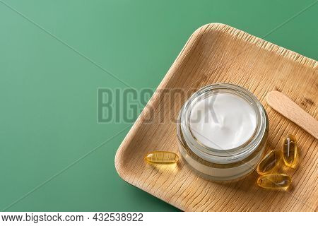 Beauty Skin Care Cream And Few Essential Oil Capsules On A Wooden Tray Over Pastel Green Background.