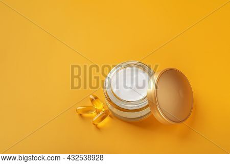 Moisturizing Skin Care Cream In An Open Glass Jar With Golden Lid And Few Essential Oil Capsules Aga