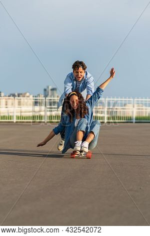 Young Caucasian Couple Enjoy Skating Together On Street. Hipster Man Pushing Back Of Woman Sitting O