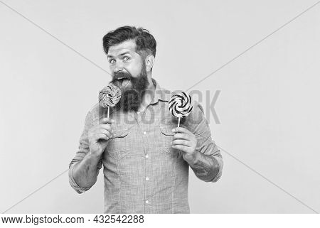 Lollipop Made For Me. Bearded Man Lick Lollipop Yellow Background. Enjoying Colorful Swirly Candy On