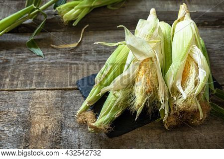 Healthy Ripe Corn On A Wooden Kitchen Table. The Concept Of A Organic Menu And Autumn Harvesting Veg