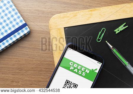 Green Pass At School Concept: Smartphone With The Text Green Pass Over A Chalkboard Sorrounded By So