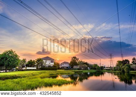 Line Of High Voltage Power With Electricity Transmission Close To Residential Buildings. Power Trans