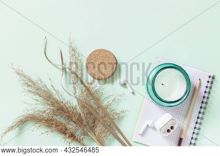 Flat Lay Still Life Aroma Candle, Pampas Grass, Notepad And Pencil On A Pastel Green Background. Moc