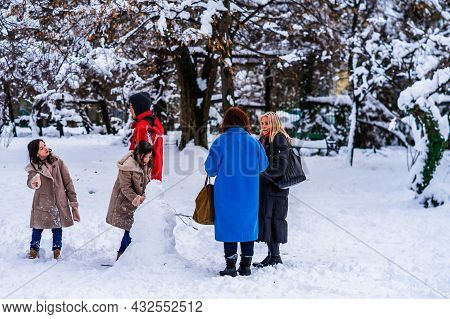 Family Building A Snowman In A Park In Bucharest, Romania, 2021