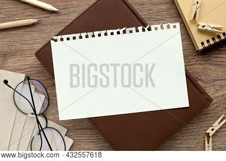 Notepad Page On Notepad On Wood Table. With Place For Text. Near Office Supplies And Glasses