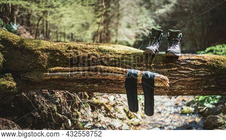 Pair Of High Trekking High-top Boot Drying Up With Wet Socks On The Felled Over Forest Creek Tree Un