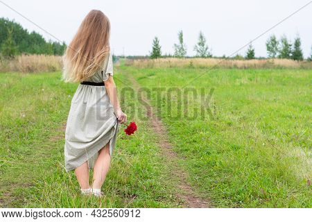 Young Blond Long Haired Woman With Red Abloom Dahlia Flower In Yand Stand On Road With Green Grass.