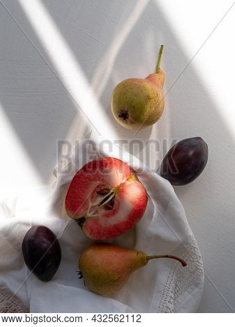 Autumn Flat Lay With Fresh Red Apples Pears Plums On White Linen Table Cloth On Light Background Wit