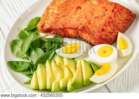 Close-up Of Oven Baked Salmon Fillet With Creamy Ripe Avocado, Baby Spinach And Hard Boiled Eggs On
