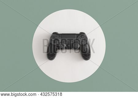 Black Wireless Controller On Green Background. Top View. Flat Lay.