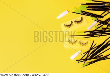 Different Tools For Eye Lash Extension On Trendy Bright Yellow Background. Fake Eyelashes, Brushes A
