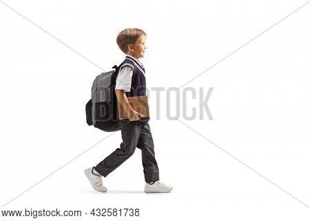 Full length profile shot of a little schoolboy in a uniform carrying a backpack and a book and walking isolated on white background