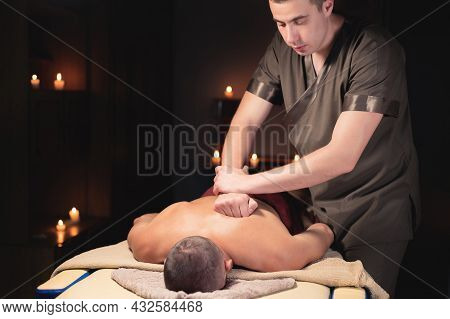 A Professional Masseur A Physiotherapist Makes A Back Massage To A Client Man In A Dark Room Of A Ma