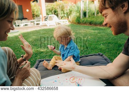 Happy Parents Showing Their Palms In Highlighter To Each Other, Their Toddler Daughter Sitting On Ma