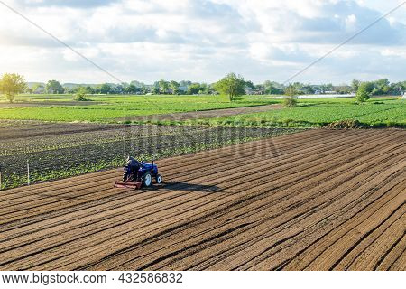 A Farmer On A Tractor Cultivates A Field. Land Cultivation. Seasonal Worker. Recruiting And Hiring E