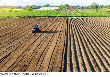 Tractor On Farmland Field. Farm Work. Milling Soil, Softening The Soil Before Planting New Crops. Pl