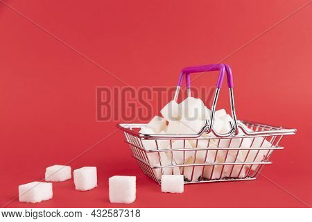 The Shopping Cart Is Filled With Refined Sugar Cubes On A Red Background. Copy Space.
